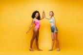 teljes hosszúságú kilátás fiatal afro-amerikai nő fürdőruhában így magas 5 szőke barát rövidnadrágban sárga