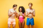izgatott multikulturális barátok nyári ruha segítségével digitális eszközök elszigetelt sárga