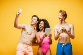 fiatal férfi csinál szelfi okostelefon többnemzetiségű barátok gazdaság digitális eszközök elszigetelt sárga