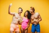 félmeztelen férfi csinál szelfi okostelefon izgatott multikulturális barátok gazdaság szerkentyű elszigetelt sárga