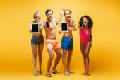 teljes hosszúságú kilátás fiatal multietnikus barátok nyári ruha mutatja modulok üres képernyő sárga