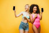 izgatott fajok közötti barátok nyári ruha mutató okostelefonok üres képernyő sárga