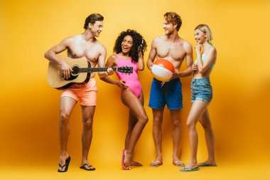 full length view of young man playing guitar near multiethnic friends in summer outfit on yellow
