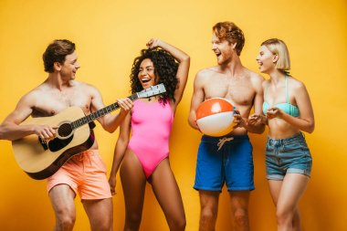 young man playing acoustic guitar near excited multiethnic friends in summer outfit on yellow