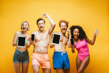 Excited multiethnic friends in summer outfit showing digital devices with blank screen on yellow stock vector