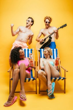 multicultural women sitting in deck chairs with cocktails near shirtless friends playing guitar and singing on yellow