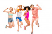 Multiethnic friends in sunglasses and swimsuits showing yeah gesture while jumping isolated on white