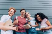 Többnemzetiségű diákok kávé menni, és könyvek nézi a kamera a városi utcában