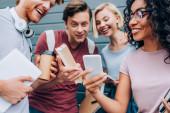 Selektivní zaměření multikulturní studenti pomocí smartphonu při držení knih a kávy jít na městské ulici