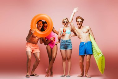 Shirtless man waving hand near excited multicultural friends with swim ring and cocktail glasses isolated on pink stock vector
