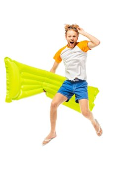 Excited man holding sunglasses and inflatable mattress while jumping isolated on white stock vector