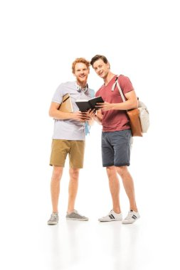 Students with notebooks and backpacks looking at camera on white background stock vector