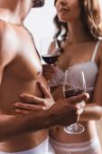 Fotografie Ausgeschnittene Ansicht eines sexy Paares in Unterwäsche, das zu Hause Weingläser hält