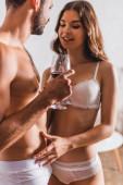 Selektiver Fokus der sexy Frau, die zu Hause Unterhosen ihres Freundes mit einem Glas Wein berührt