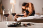 Selektiver Fokus des Eherings auf Portemonnaie in der Nähe von Smartphone und Weingläsern mit hemdslosem Mann, der Frau im Bett umarmt