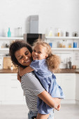 african american girl looking at camera and embracing mother holding her on hands in kitchen
