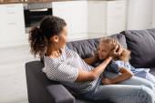 junge afrikanisch-amerikanische Mutter berührt Kopf ihrer aufgeregten Tochter, während sie zu Hause auf dem Sofa sitzt