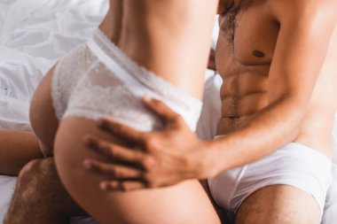 Cropped view of muscular man touching butt of girlfriend in panties on bed stock vector