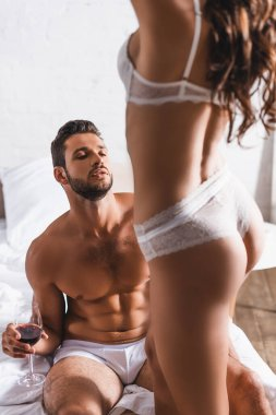 Selective focus of muscular man underpants holding glass of wine near sexy woman on bed