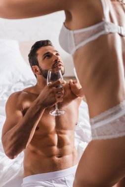 Selective focus of woman in lingerie touching muscular boyfriend with glass of wine on bed stock vector