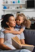 szelektív fókusz afro-amerikai dadus gazdaság könyv és nézi lány átöleli őt a konyhában