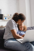 selective focus of african american freelancer kissing upset daughter while sitting on sofa with laptop