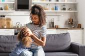 mladá africká americká žena v pruhovaném tričku dotýkající se hlavy dcery, zatímco sedí doma na pohovce