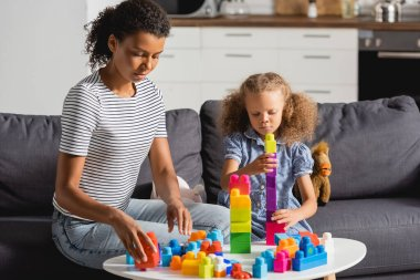 Young african american babysitter and girl playing with colorful building blocks while sitting on sofa stock vector