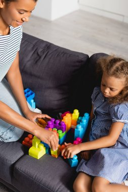 High angle view of african american child with nanny playing with multicolored building blocks on sofa stock vector