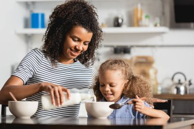 Young african american mother in striped t-shirt pouring milk into bowl near daughter holding spoon stock vector