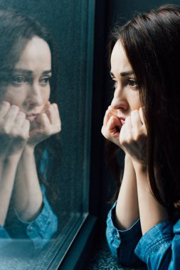 Sad brunette woman touching face while looking at window stock vector