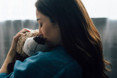 rozrušená brunetka žena se zavřenýma očima objímající medvídka