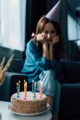 selective focus of birthday cake on coffee table near upset woman