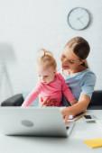 Szelektív fókusz anya gazdaság baba lány közelében szerkentyűk az asztalon