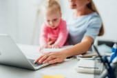 Selektive Fokussierung von Freiberuflern mit Laptop und Baby-Mädchen am Tisch