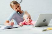Szelektív fókusz a csecsemő ül anya közelében beszél okostelefonon, és otthon dolgozik