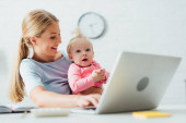 Selective focus of mother looking at baby girl while working with laptop at table