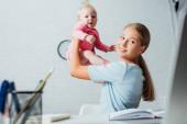 Selektivní zaměření ženy při pohledu na notebook při hraní s nemluvně dcera doma