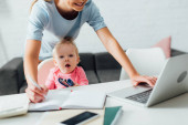 Selektiver Fokus der Frau mit Laptop und Schreiben auf Notizbuch in der Nähe der kleinen Tochter mit Heftklammer