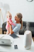 Selektivní zaměření matky drží holčičku v blízkosti gadgets, notebook a zvlhčovač na stole