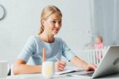 Selektiver Fokus der Frau, die mit Laptop und Notebook in der Nähe des Babyfons auf dem Tisch arbeitet