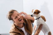 excited businessman in wireless headphones touching jack russell terrier dog in office
