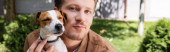 panoramic shot of man cuddling jack russell terrier dog while looking at camera