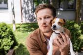mladý muž při pohledu na kameru při mazlení jack russell teriér pes venku