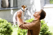 young man standing outdoors and raising jack russell terrier dog on hands