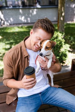 man with closed eyes sitting on bench, cuddling jack russell terrier dog and holding paper cup