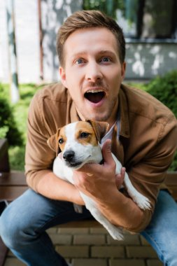 excited man with open mouth looking at camera while holding jack russell terrier dog