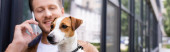 website header of man with jack russell terrier dog talking on mobile phone on street