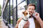 selective focus of young man holding jack russell terrier dog and talking on smartphone outdoors