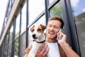 selektivní zaměření mladý muž mluví na smartphone, zatímco drží jack Russell teriér pes na ulici